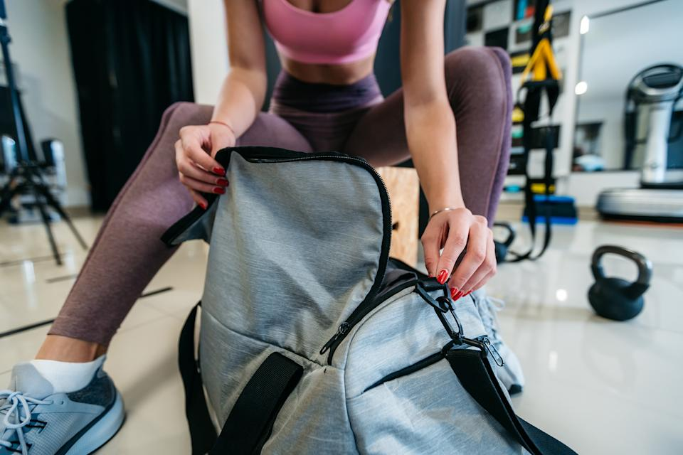Young slim attractive caucasian woman opening her gym bag in a gym.