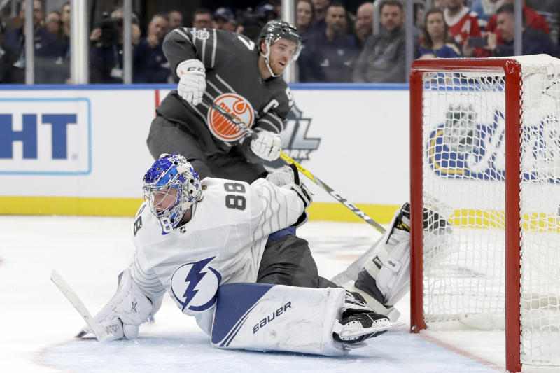 Tampa Bay Lightning goalie Andrei Vasilevskiy (88) reaches back to block a shot by Edmonton Oilers forward Connor McDavid (97) in the NHL hockey All Star final game Saturday, Jan. 25, 2020, in St. Louis. (AP Photo/Jeff Roberson)