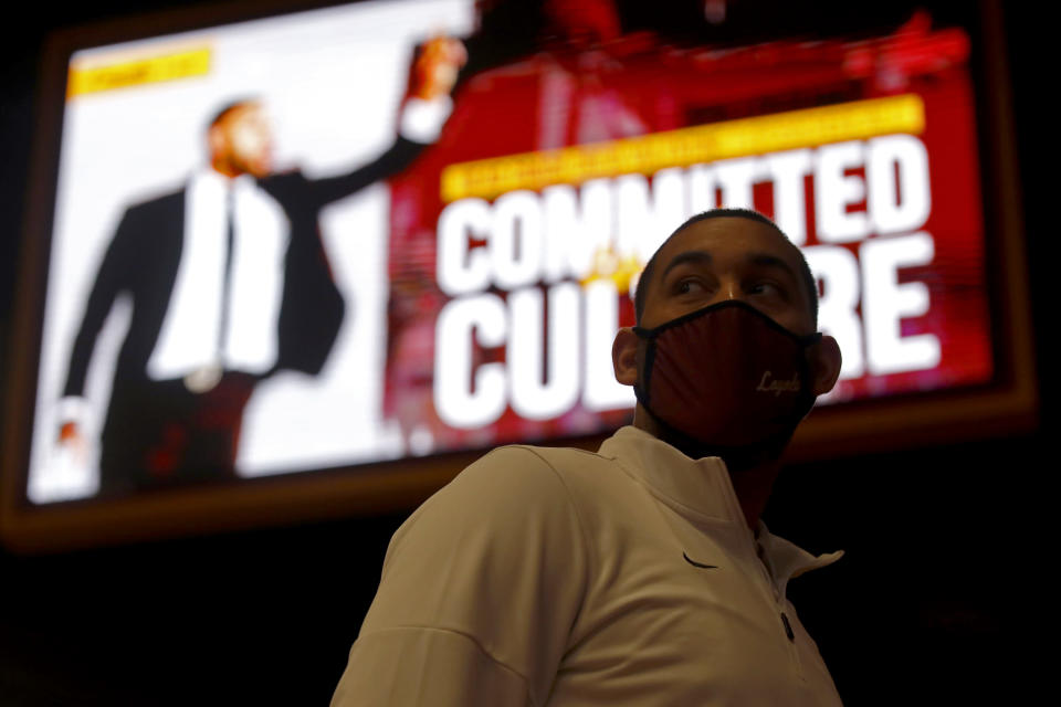 Drew Valentine is partially silhouetted against an illuminated LED board after a press conference where he was introduced as Loyola's new men's NCAA college basketball head coach, Tuesday, April 6, 2021, in Chicago. (AP Photo/Shafkat Anowar)
