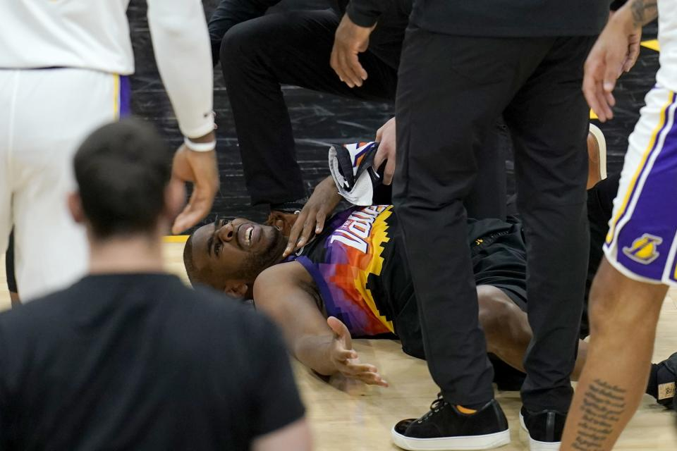 An injured Phoenix Suns guard Chris Paul grimaces in pain during the first half of Game 1 of their NBA basketball first-round playoff series against the Los Angeles Lakers Sunday, May 23, 2021, in Phoenix. (AP Photo/Ross D. Franklin)