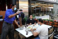 A worker wearing a protective face mask and gloves serves food at a restaurant during the reopening of malls, following the outbreak of the coronavirus disease (COVID-19), at Mall of the Emirates in Dubai
