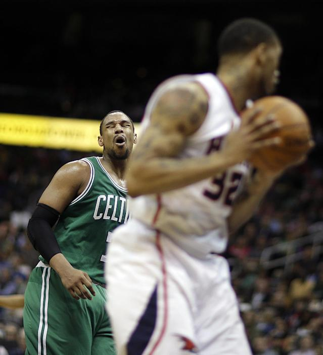 Boston Celtics' Jared Sullinger, left, reacts after missing a shot as the rebound falls into the hands of Atlanta Hawks' Mike Scott, right, in the third quarter of an NBA basketball game, Wednesday, April 9, 2014, in Atlanta. (AP Photo/David Goldman)