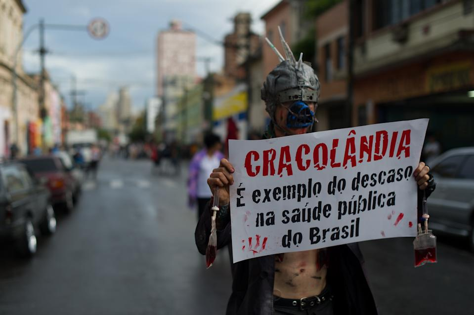 """A demonstrator holds a banner reading """"Cracolandia is an example of the failure of Brazilian public health policy"""" during a demonstration against paramilitary police's clean-up operation in the area called """"Cracolandia"""" (Crackland) in downtown Sao Paulo, Brazil on January 14, 2012. AFP PHOTO / Yasuyoshi Chiba (Photo credit should read YASUYOSHI CHIBA/AFP via Getty Images)"""