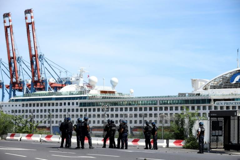 French police officers face demonstrators in Le Port on March 1, 2020, as people protest passengers from the Sun Princess cruise ship on the Indian Ocean island of La Reunion disembarking without having temperatures checked; The incident came hours after clashes between police and protesters near the airport in Martinique