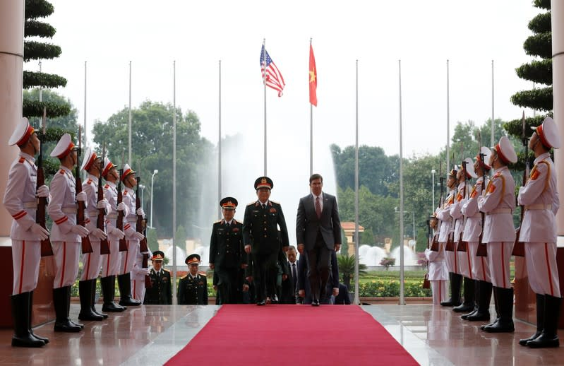 U.S. Defense Secretary Mark Esper and Vietnam's Defence Minister General Ngo Xuan Lich enter the meeting room in Hanoi