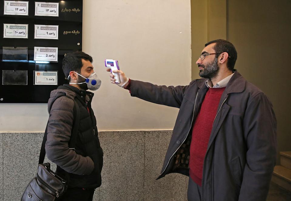 An Iranian man checks the temperature of a person entering an office building in Tehran on March 4, 2020. - Iran has scrambled to halt the rapid spread of the COVID-19 virus, shutting schools and universities, suspending major cultural and sporting events, and cutting back on work hours. (Photo by ATTA KENARE / AFP) (Photo by ATTA KENARE/AFP via Getty Images)