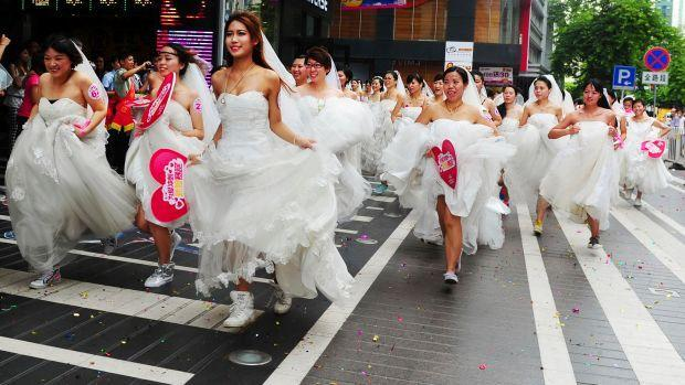 Women in wedding gowns participate in a brides' race event organized by a shopping mall to celebrate the upcoming Qixi Festival in Guangzhou