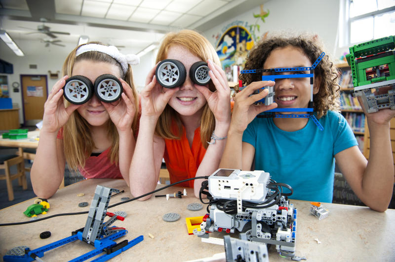 Three little girls playing with Meccano.