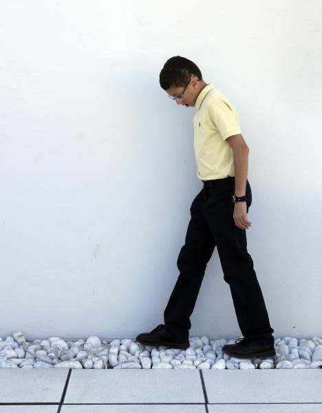 Jake Finkbonner, of Ferndale, Washington, walks on cobblestones prior to an interview with the Associated Press, in Rome, Thursday, Oct. 18, 2012. Jake was infected with a flesh-eating bacteria in 2006, when he was five years old, and his prognosis was so grave that his parents had last rites performed and were discussing donating his organs. The Vatican determined that Jake's cure was a miracle due to the intercession of Kateri Tekakwitha, a 17th century Native American who is among seven people who will be declared saints on Sunday by Pope Benedict XVI. (AP Photo/Alessandra Tarantino)