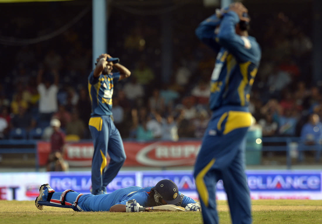 Sri Lankan cricketers react failing a chance to run-out Indian Ishant Sharma (on the ground) during the final match of the Tri-Nation series between India and Sri Lanka at the Queen's Park Oval stadium in Port of Spain on July 11, 2013. India defeated Sri Lanka by 1 wicket to win the series. AFP PHOTO/Jewel Samad
