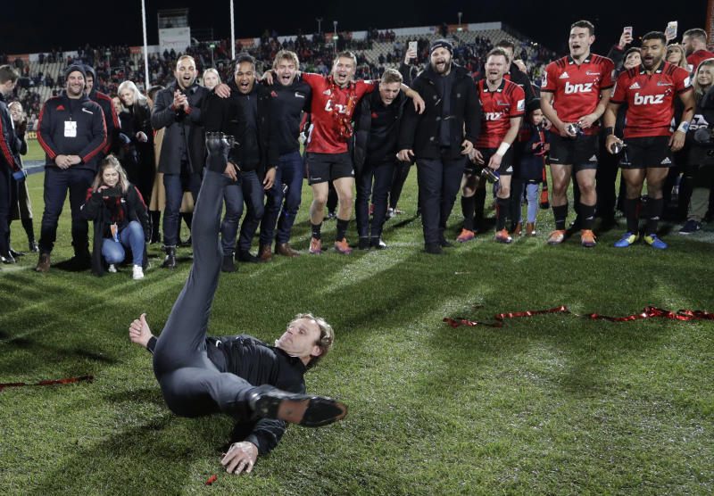 Crusaders coach Scott Robertson performs a break-dance as celebrates his team's 19-3 win in the Super Rugby final between the Crusaders and the Jaguares in Christchurch, New Zealand, Saturday, July 6, 2019. (AP Photo/Mark Baker)