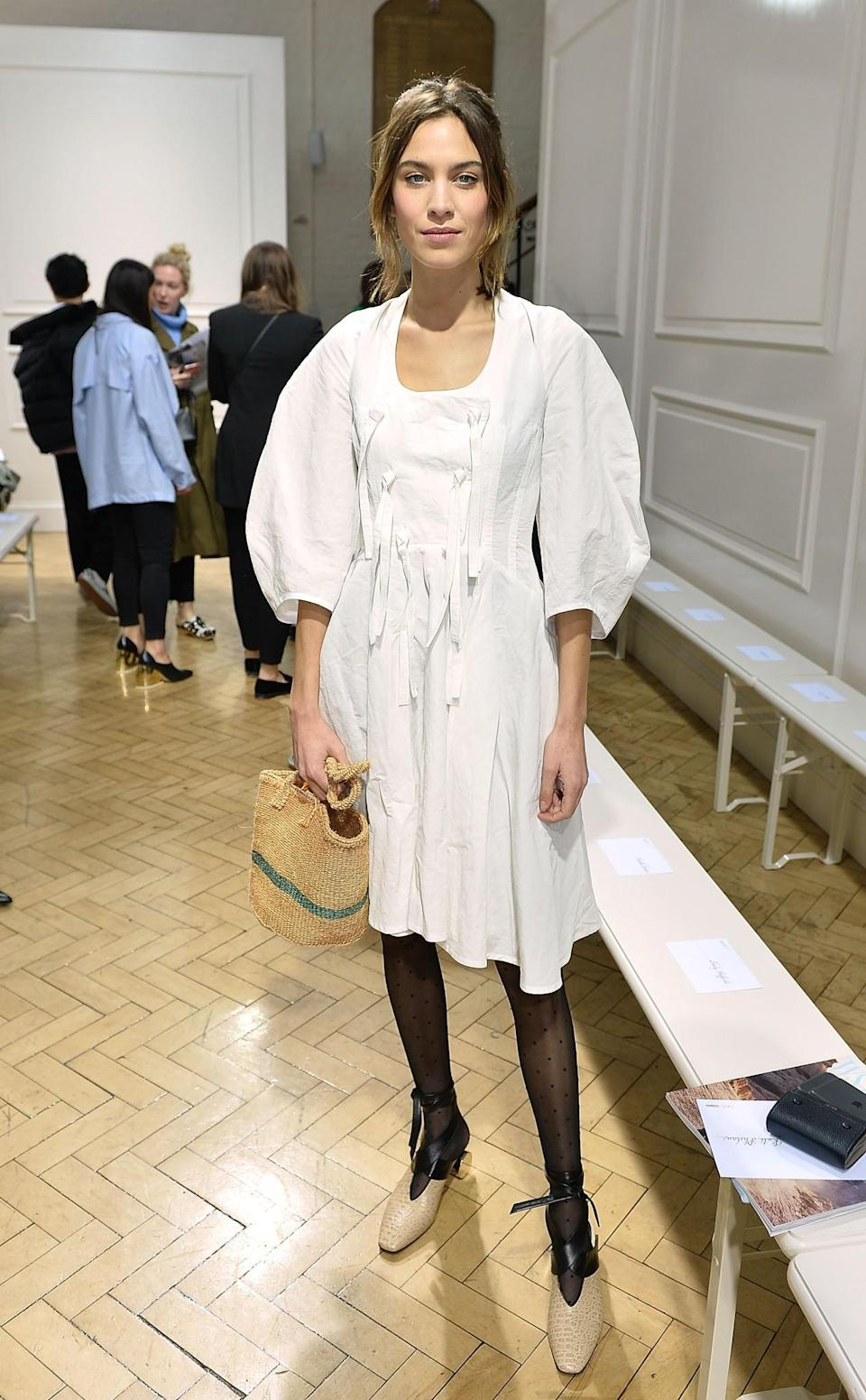<p>Alexa Chung wore a puffy-sleeved white dress and carried a chic straw bag. <i>[Photo: Getty]</i> </p>
