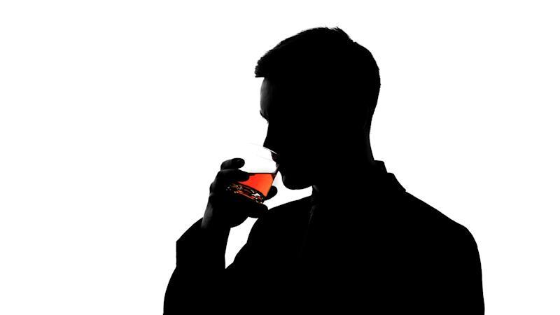 Silhouette of business man drinking whiskey, enjoying taste of aged beverage. Photo: Getty
