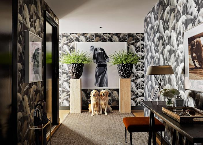 """""""The whole apartment is basically glass walls, so we wanted the entrance to feel cozy and intimate,"""" says Deutsch. """"We painted the moldings and all of the doors this high-gloss black so you'd have that juxtaposition with the light as you turn the corner. We're not afraid of the wow factor."""" Oversize planters sit on travertine pillars and flank a Bert Stern photo of Marilyn Monroe. The palm jungle wallpaper is from <a href=""""https://www.cole-and-son.com/en"""" rel=""""nofollow noopener"""" target=""""_blank"""" data-ylk=""""slk:Cole and Son"""" class=""""link rapid-noclick-resp"""">Cole and Son</a> and the ottoman is by <a href=""""http://www.liaigre.com/en/"""" rel=""""nofollow noopener"""" target=""""_blank"""" data-ylk=""""slk:Christian Liaigre"""" class=""""link rapid-noclick-resp"""">Christian Liaigre</a>."""