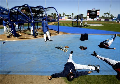 Atlanta Braves infielder Juan Francisco, center, stretches as New York Mets players take batting practice before an exhibition spring training baseball game, Monday, March 4, 2013, in Port St. Lucie, Fla. (AP Photo/Julio Cortez)