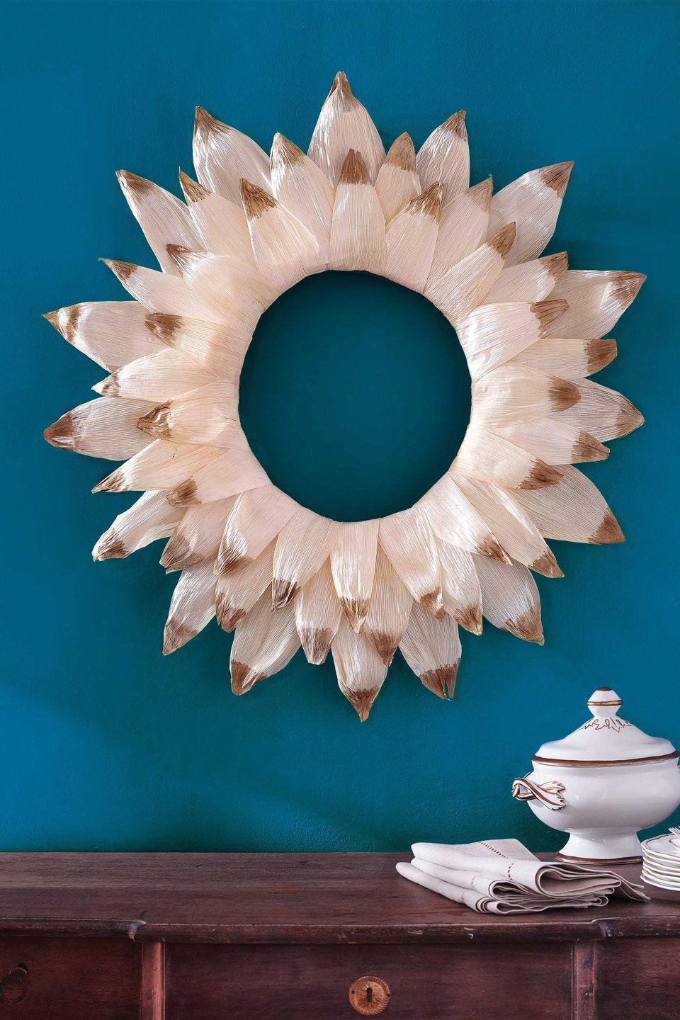 <p>Paint the tips for an elegant twist on this harvest staple.</p><p><strong>Step 1: </strong>Wrap corn husks around an 18-inch diameter straw wreath, using a hot-glue gun to adhere the edges. You'll need about 35 husks to completely cover the wreath form.</p><p><strong><strong>Step 2: </strong> </strong>Using a foam brush, paint the tips of 48 additional corn husks with gold acrylic paint; let dry (about 15 minutes).</p><p><strong>Step 3: </strong> Starting with the outer edge of the wreath, use hot-glue to adhere three concentric rings of 16 corn husks each. (Attach the second ring to the middle of the wreath and the third to its inner edge.) For the second and third rings, position the tip of each corn husk between two corn husks from the previous ring.</p>