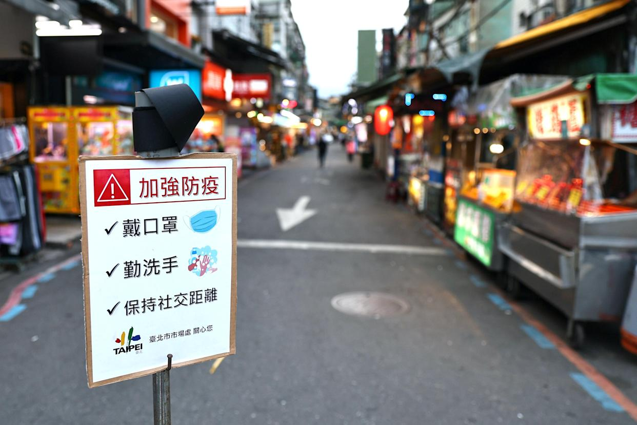 A sign reminding people to wear protective face masks, wash hands and keep social distancing is placed in front of a night market, amid an increasing number of COVID-19 infections, in Taipei, Taiwan, May 15, 2021. REUTERS/Ann Wang