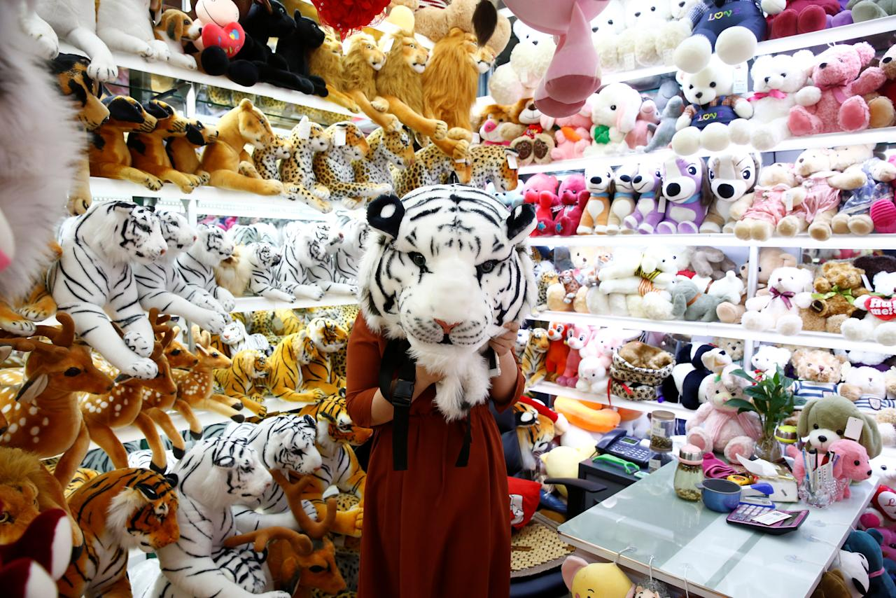 A staff member holds up a toy tiger head as she poses for a picture in a stall at the Yiwu Wholesale Market in Yiwu, Zhejiang province, China, April 28, 2017. Picture taken April 28, 2017. REUTERS/Thomas Peter     TPX IMAGES OF THE DAY