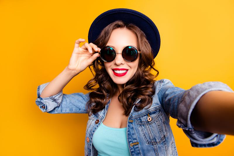 A young woman in a hat and sunglasses takes a selfie.