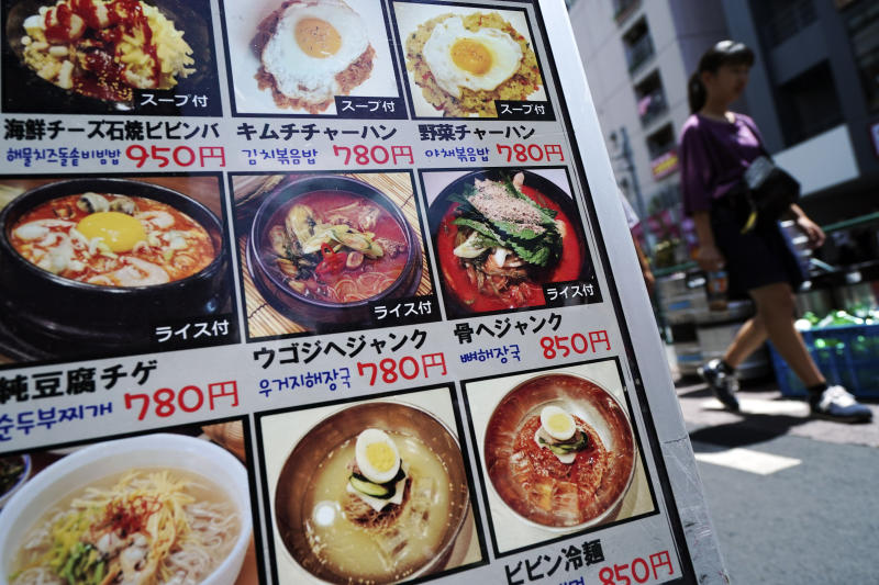 In this Aug. 13, 2019, photo, a woman walks past a menu of South Korean restaurant in Shin Okubo area in Tokyo. Tokyo's Shin Okubo district bustles with Korean restaurants and stores selling K-pop merchandise. (AP Photo/Eugene Hoshiko)