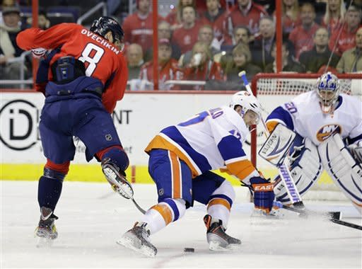 Washington Capitals left wing Alex Ovechkin (8), from Russia, can't keep control of the puck as New York Islanders' Andrew MacDonald (47) defends during the first period of an NHL hockey game Tuesday, March 26, 2013, in Washington. (AP Photo/Alex Brandon)
