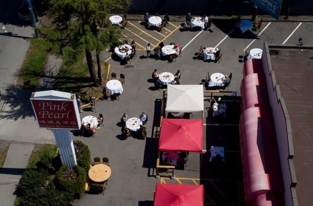 People eat lunch in the parking lot outside the Pink Pearl Chinese restaurant, in Vancouver, on Tuesday, May 25, 2021. (Darryl Dyck/Canadian Press - image credit)
