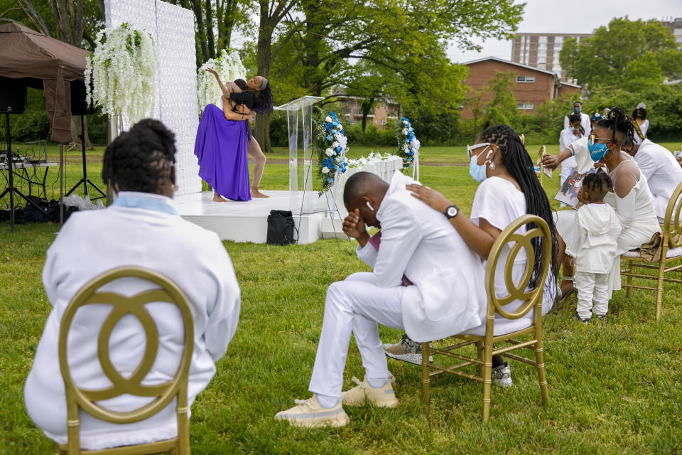 As dancers EbonyTye Hamilton and Samaree Lawson perform, the family of Joanne Paylor, 62, of Washington, mourns their loss, at Cedar Hill Cemetery in Suitland-Silver Hill, Md., Sunday, May 3, 2020, during a socially distanced outdoor memorial service. The family delayed Paylor's funeral for almost two months hoping the social distancing rules would be lifted. Despite not having died from coronavirus, almost every aspect of her funeral has been impacted by the pandemic. (AP Photo/Jacquelyn Martin)