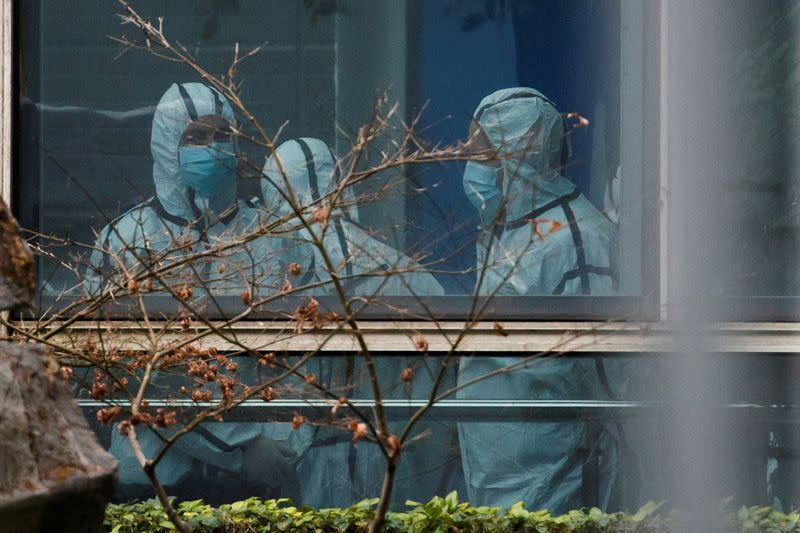 Members of the World Health Organization (WHO) team don personal protection suits during a visit at the Hubei Animal Epidemic Disease Prevention and Control Center in Wuhan