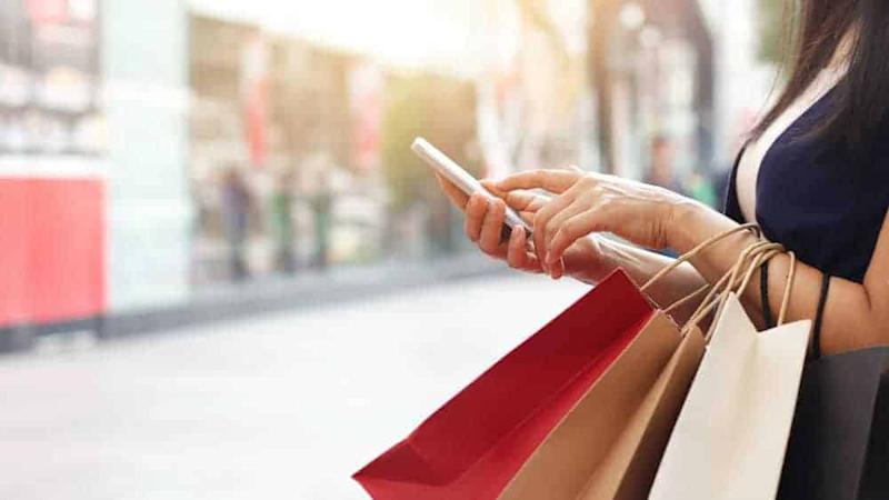 Lady holding mobile phone and shopping bags
