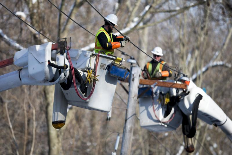 Linesmen work to restore electrical power, Friday, Feb. 7, 2014, in Downingtown, Pa. A small army of electricity restoration crews labored Friday to reconnect about 330,000 customers in Pennsylvania and Maryland. (AP Photo/Matt Rourke)