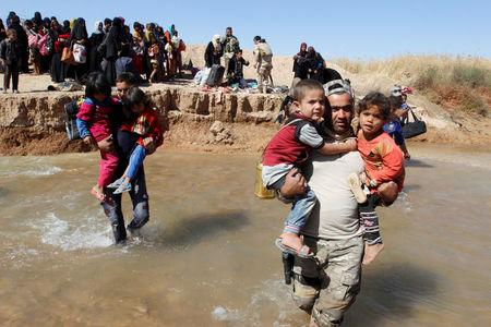 A member of Kurdish Peshmerga forces (R) helps people, who fled from their homes in Hawija, as they arrive to be transported to camps for displaced people, in southwest of Kirkuk, Iraq October 4, 2017. REUTERS/Ako Rasheed