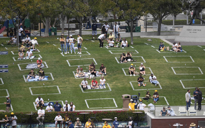 Baseball fans sit in social distance squares during a baseball game between the Arizona Diamondbacks and the San Diego Padres Thursday, April 1, 2021, on opening day in San Diego. (AP Photo/Denis Poroy)