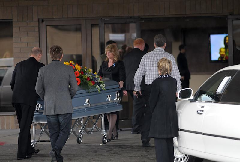A casket with the bodies of  Charlie and Braden  Powell, ages 7 and 5,  is wheeled into Life Center Church in Tacoma Saturday  Feb. 11, 2012.   The family of missing Utah woman Susan Powell is holding a public funeral for her two sons, nearly a week after their father killed them in a gas-fueled blaze.  Hundreds of people are attending the Saturday service.  Many are wearing purple and blue ribbons in memory of 7-year-old Charlie and 5-year-old Braden. Family members and the boys' teachers are scheduled to speak. The boys' remains are in one coffin adorned with flowers. They were killed in a fire set by their father, Josh Powell, when they went to visit him Sunday at his home in Graham. (AP Photo/The News Tribune, Dean J. Koepfler)
