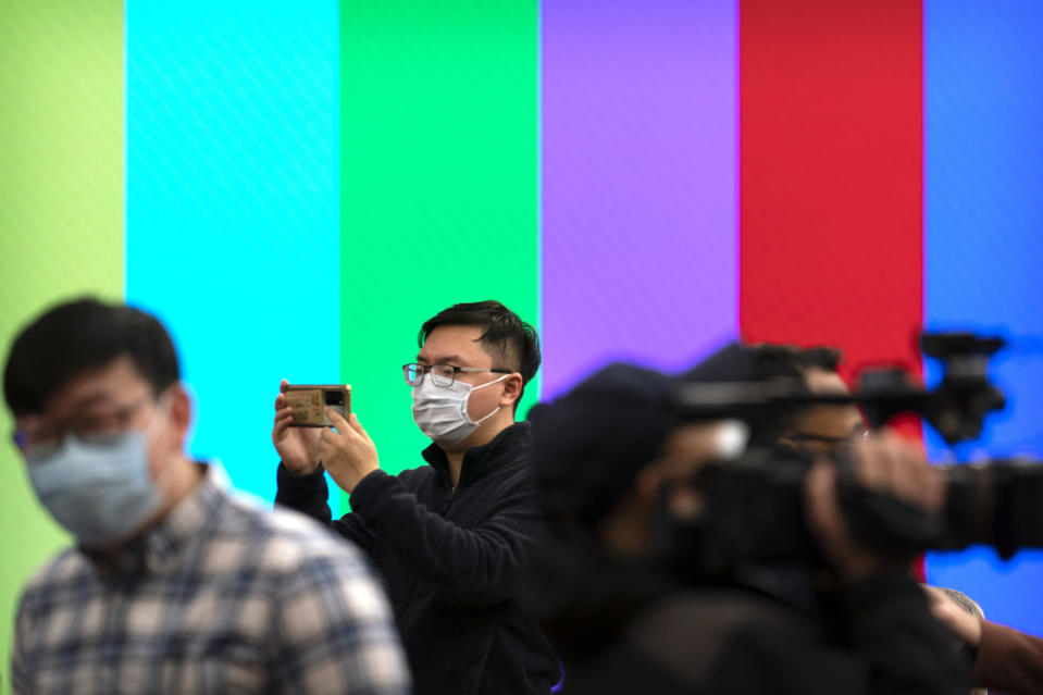 A journalist takes a smartphone photo before a remote video press conference by Chinese Foreign Minister Wang Yi held on the sidelines of the annual meeting of China's National People's Congress (NPC) in Beijing, Sunday, March 7, 2021. (AP Photo/Mark Schiefelbein)