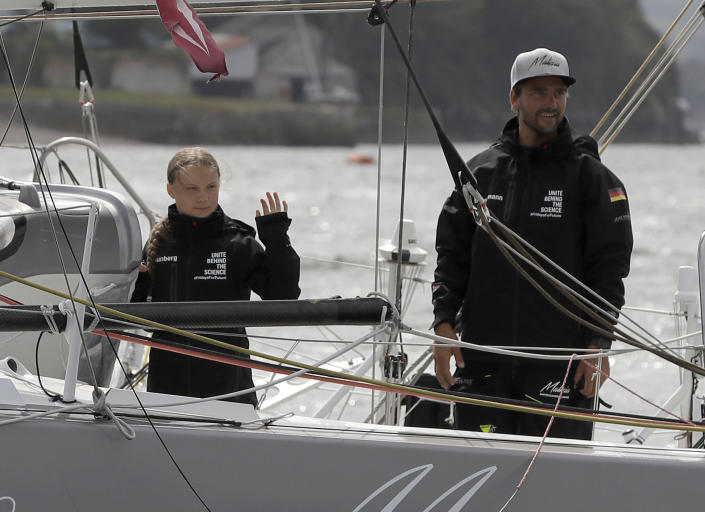 Climate change activist Greta Thunberg and skipper Boris Herrmann wave from the Malizia II boat in Plymouth, England, Wednesday, Aug. 14, 2019. The 16-year-old climate change activist who has inspired student protests around the world will leave Plymouth, England, bound for New York in a high-tech but low-comfort sailboat.(AP Photo/Kirsty Wigglesworth, pool)