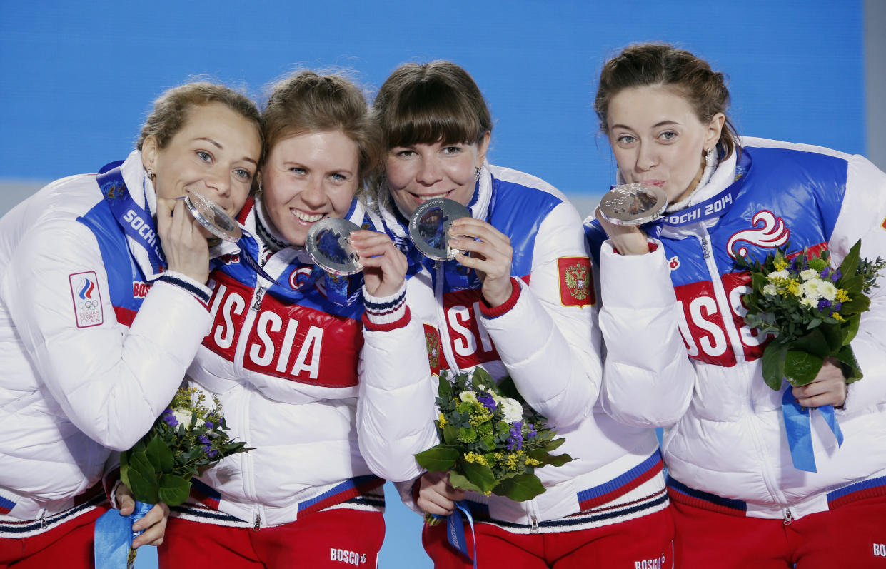 Silver medalists Olga Zaitseva, far left, Yana Romanova, Ekaterina Shumilova and Olga Vilukhina of Russia pose during the ceremony at the 2014 Winter Olympics in Sochi. (Photo: Eric Gaillard/Reuters)