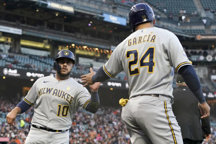 Milwaukee Brewers' Omar Narvaez (10) celebrates with Avisail Garcia (24) after both scored on a two-run single by Lorenzo Cain during the second inning of the team's baseball game against the San Francisco Giants in San Francisco, Wednesday, Sept. 1, 2021. (AP Photo/Jeff Chiu)