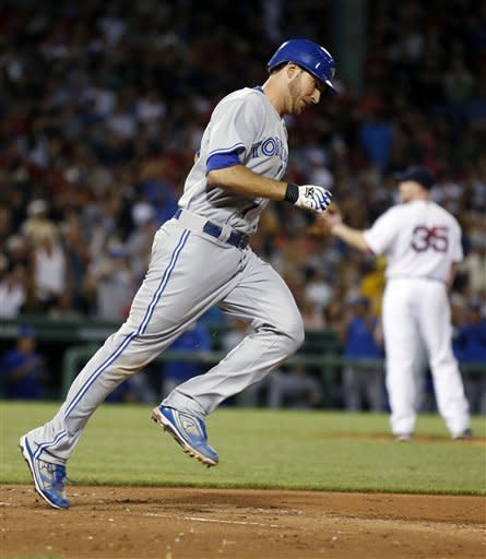 Toronto Blue Jays' J.P. Arencibia, foreground, rounds first base on a solo home run off Boston Red Sox's Aaron Cook (35) in the seventh inning of a baseball game in Boston, Saturday, July 21, 2012. (AP Photo/Michael Dwyer)