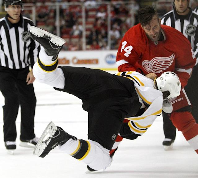 Detroit Red Wings right wing Todd Bertuzzi (44) takes down Boston Bruins defenseman Mike Moore during a fight in the first period of a preseason NHL hockey game Saturday, Sept. 21, 2013 in Detroit. (AP Photo/Duane Burleson)