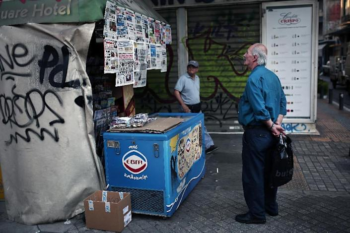 A man reads newspapers headlines in the center of Athens on June 17, 2015 (AFP Photo/Angelos Tzortzinis)