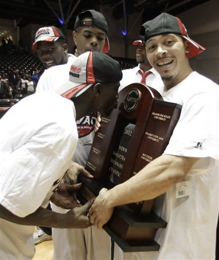 Mississippi Valley State 's William Pugh, kisses the trophy as Kevin Burwell smiles at the camera following their 71-69 win over Texas Southern in an NCAA college basketball game in championship of the Southwestern Athletic Conference tournament, Saturday, March 10, 2012, in Garland, Texas. (AP Photo/Tony Gutierrez)