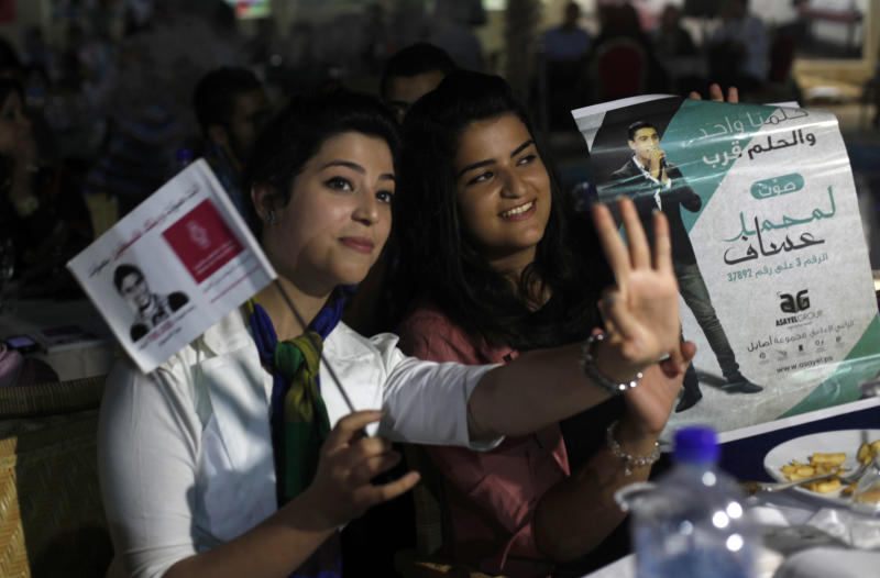 "Palestinians hold pictures of Palestinian singer Mohammed Assaf while watching the contestant perform in a regional TV singing contest, in Gaza City, Saturday, June 22, 2013. Palestinians relished a rare moment of pride and national unity Saturday after the 23-year-old wedding singer from a refugee camp in the Gaza Strip won ""Arab Idol,"" a regional TV singing contest watched by millions of people. (AP Photo/Hatem Moussa)"