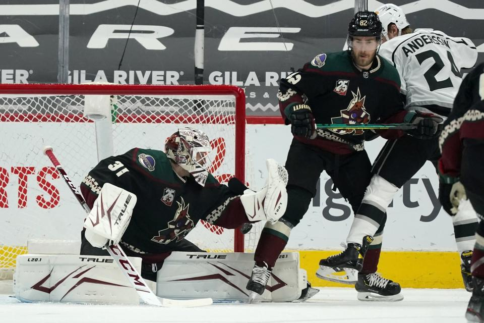 A shot by Los Angeles Kings' Gabriel Vilardi, not seen, slips past Arizona Coyotes goaltender Adin Hill (31) for a goal as Coyotes defenseman Jordan Oesterle (82) and Kings center Lias Andersson (24) work for position during the first period of an NHL hockey game Wednesday, May 5, 2021, in Glendale, Ariz. (AP Photo/Ross D. Franklin)
