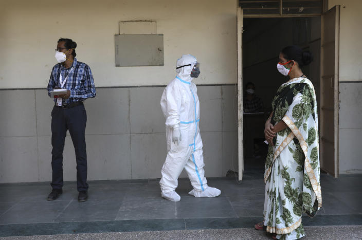 A health worker takes a brief break in between testing for COVID-19 at a testing center in New Delhi, India, Saturday, Oct. 3, 2020. India has crossed 100,000 confirmed COVID-19 deaths on Saturday, putting the country's toll at nearly 10% of the global fatalities and behind only the United States and Brazil. (AP Photo/Manish Swarup)