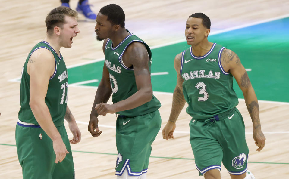 Dallas Mavericks guard Luka Doncic (77), forward Dorian Finney-Smith (10), and guard Trey Burke (3) celebrate after their team took the lead over the Washington Wizards late in the second half of an NBA basketball game Saturday, May 1, 2021, in Dallas. (AP Photo/Ron Jenkins)