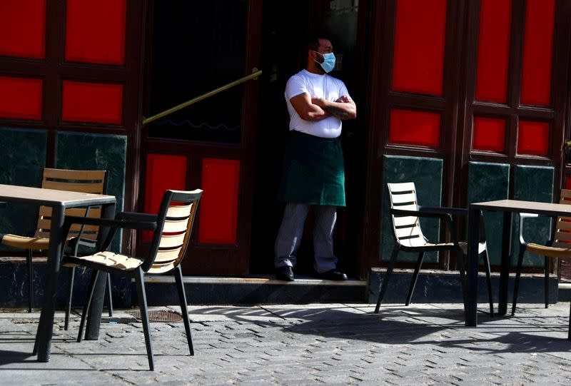 FILE PHOTO: FILE PHOTO: FILE PHOTO: A waiter wearing a protective face mask waits for customers in his terrace amid the outbreak of the coronavirus disease (COVID-19) in Madrid