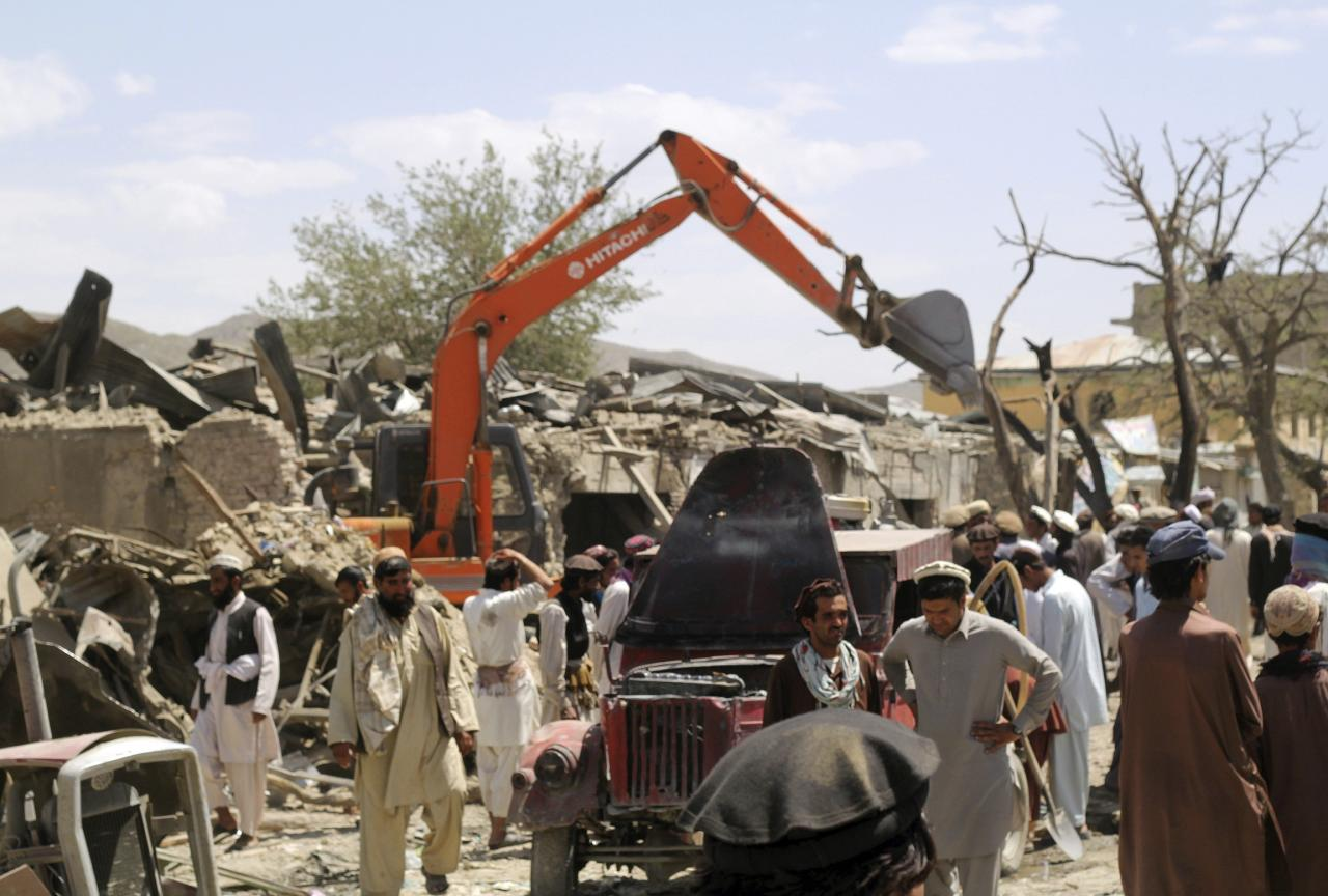 Villagers gather at the site of a car bomb attack in Urgon district eastern province of Paktika July 15, 2014. A car packed with explosives exploded on Tuesday as it sped through a crowded market in Afghanistan's eastern province of Paktika, killing at least 89 people, officials said, one of the most violent attacks in the country in a year. REUTERS/Stringer (AFGHANISTAN - Tags: CIVIL UNREST POLITICS)