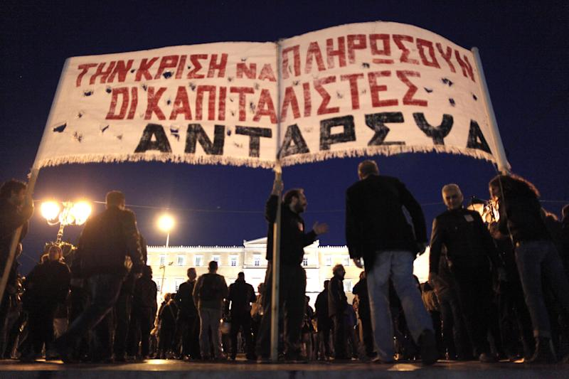 "Demonstrators hold a banner reading ""Let the capitalists pay for the crisis"" outside of the Greek Parliament, seen in background, in Athens on Sunday Nov. 11, 2012.  Greece's lawmakers were set today to pass next year's austerity budget, extending tough spending cuts measures that have already left Greeks struggling as the country tries to slash its debts and pull itself out of a severe recession.(AP Photo/Petros Giannakouris)"