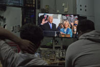 People watch the inauguration of U.S. President Joe Biden on a television at a coffee shop in Medan, North Sumatra, Indonesia, late Wednesday, Jan. 20, 2021. (AP Photo/Binsar Bakkara)