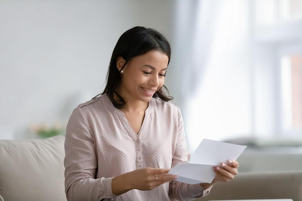 Woman smiling at a letter
